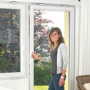 Eine Frau kippt eine Balkontür an, die mit einem Einbruchschutz gesichert ist.