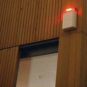 Eine Alarmanlage mit leuchtendem Alarmlicht ist an der Außenwand eines Hauses neben einem Fenster angebracht, als Symbolbild für vernetzte Sicherheitstechnik in einem Smart House.