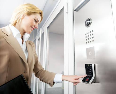 Eine Frau bedient einen Biometrieleser, der als elektronischer Einbruchschutz eines Bürogebäudes dient.