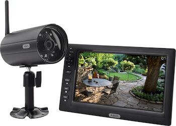 Eine Funk-Überwachungskamera ist neben einem Bildschirm abgebildet, der das Bild eines Gartens zeigt.