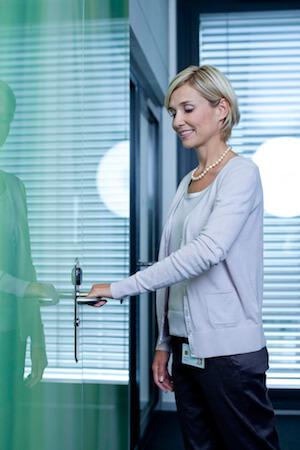 Frau klinkt Tür auf als Symbol für Türsicherung