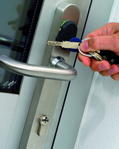 Eine Tür mit einem Schutzbeschlag zur Einbruchsicherung wird aufgeschlossen