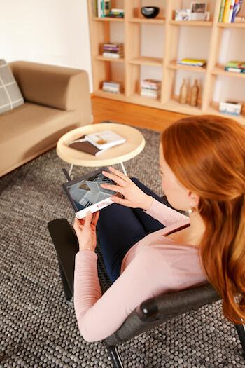 Eine Frau sitzt im Wohnzimmer mit einem Monitor, der als Teil der Haussicherheitstechnik die Videoüberwachung des Außenbereichs zeigt.