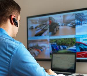 Ein Sicherheitsmann sitzt vor einem Bildschirm, auf dem Bilder von verschiedenen Funk-Überwachungskameras zu sehen sind.
